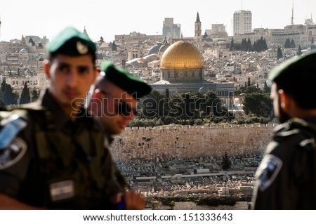 JERUSALEM - MARCH 24: Israeli soldiers occupy a street overlooking the Dome of the Rock and the Old City of Jerusalem during the annual Palm Sunday procession, March 24, 2013. - stock photo