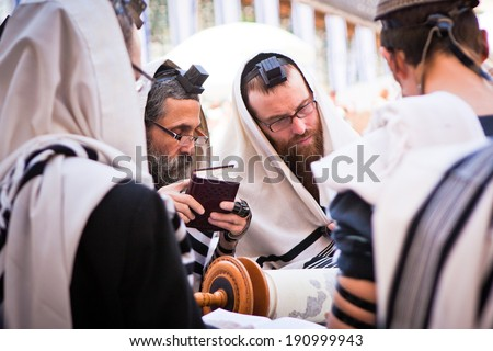 JERUSALEM - MAY 16: Orthodox Jewish men pray at western wall on May 16, 2011. The Western wall is an important Jewish religious site located in the Old City of Jerusalem - stock photo