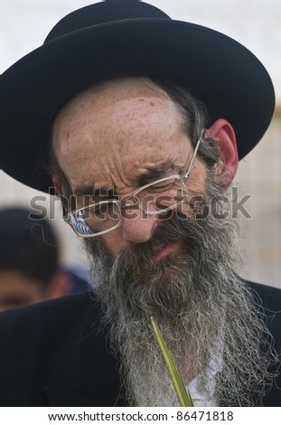 "JERUSALEM - OCT 10 : Ultra-Orthodox Jewish man inspect the ""Lulav"" in a market in Jerusalem on October 10 2011, ""Lulav"" is one of four species used during the Jewish celebration of ""Sukkot"" - stock photo"