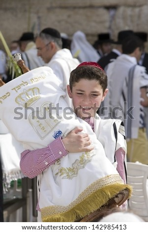 JERUSALEM, Oct. 2: Unknown boy at the Western Wall holding a Torah during the Jewish holiday of Sukkot, October 2, 2012 in Jerusalem, Israel - stock photo