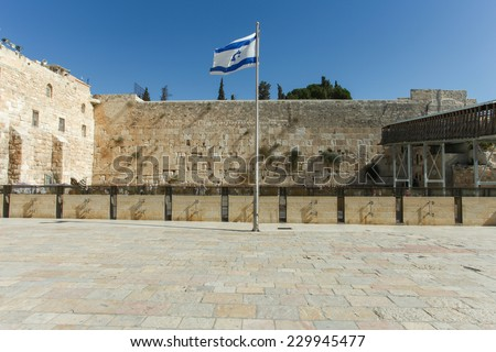 Jerusalem's wailing wall compound with blue sky, the Israeli flag and the wailing wall in the background  - stock photo