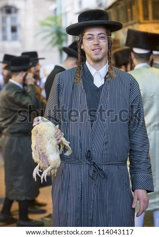 JERUSALEM - SEP 25 : An ultra Orthodox Jewish man holds chicken during the Kaparot ceremony held in Jerusalem Israel in September 25, 2012 - stock photo