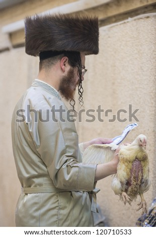 JERUSALEM - SEP 25 : An ultra Orthodox Jewish man prays with a chicken during the Kaparot ceremony held in Jerusalem Israel in September 25 2012 - stock photo
