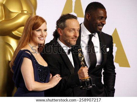 Jessica Chastain, Emmanuel Lubezki and actor Idris Elba pose in the press room during the 87th Annual Academy Awards at Loews Hollywood Hotel on February 22, 2015 in Hollywood, California. - stock photo