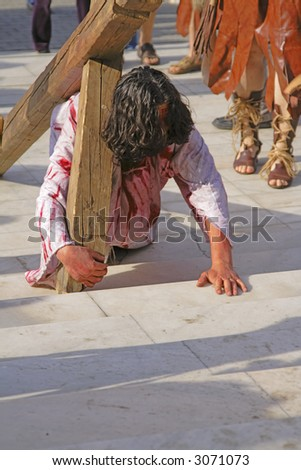 Jesus carrying the cross - aspect from a religious street show. - stock photo