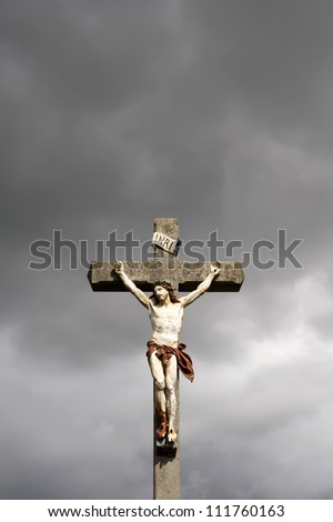 Jesus Christ crucifixion sculpture against dark clouds - stock photo