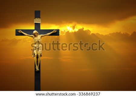 Jesus Christ on the cross over sky background with a shining celestial light from above - stock photo