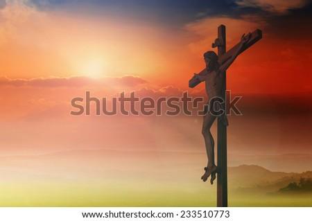 Jesus christ on the cross over sunset background. - stock photo