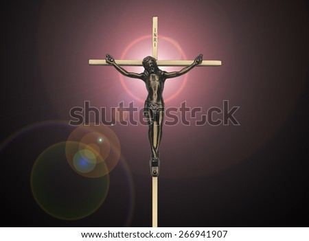 Jesus Christ passion on the cross on black with pink lens flare - stock photo