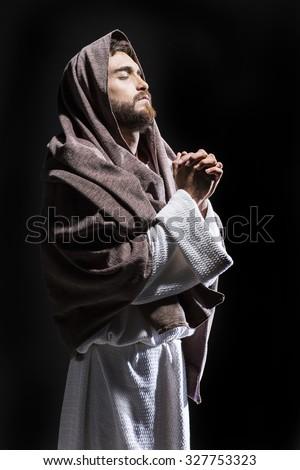 Jesus Christ praying to God in the dark black night - stock photo