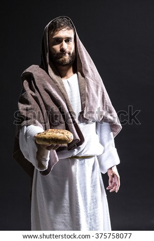Jesus Christ praying to God smilingly with bread  in the dark black night - stock photo