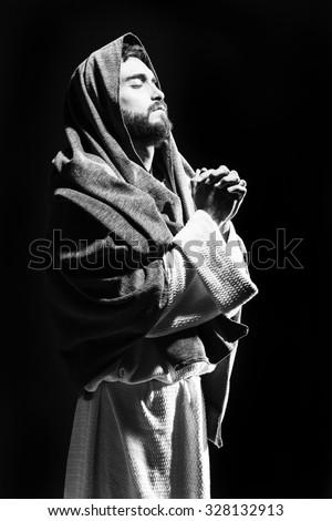 Jesus Christ praying to God w in the dark black night. Black and white - stock photo