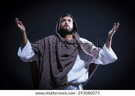 Jesus Christ praying to God with open arms in the dark blue night - stock photo
