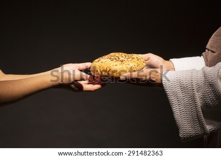 Jesus Christ sharing your bread with the hungry in the dark black night - stock photo