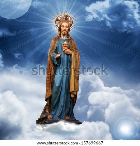 jesus christ  statue blue sky clouds background - stock photo