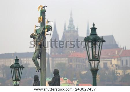 Jesus Christ statue on Charles bridge in cloudy autumn day, Prague, Czech Republic - stock photo