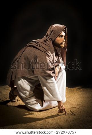 Jesus Christ writing in the sand in the dark black night - stock photo