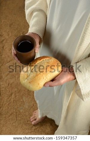 Jesus hands holding bread and cup of wine - stock photo