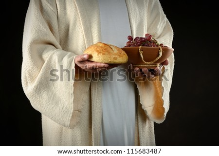 Jesus hands holding bread and grapes, symbols of communion - stock photo