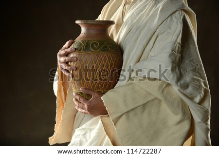 Jesus Holding a jug of water on a dark background - stock photo