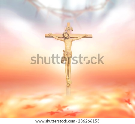 Jesus on the cross over blurred crown of thorns over beautiful sunset background. - stock photo
