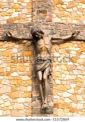 Jesus on the cross, stone church statue - stock photo