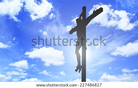 Jesus on the cross with blue sky and clouds - stock photo