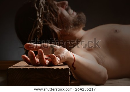 Jesus on the cross with focus on hand and nail - stock photo