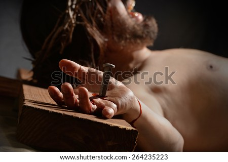 Jesus  on the cross with nail and hand in foreground - stock photo