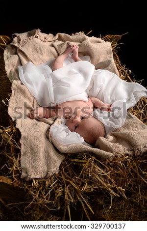 Jesus resting on a manger over dark background - stock photo