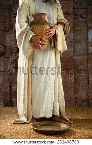 Jesus standing and holding water jar ready to wash the disciples' feet - stock photo