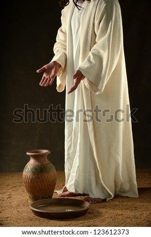 Jesus standing with hands extended and pointing to a jar and bowl - stock photo