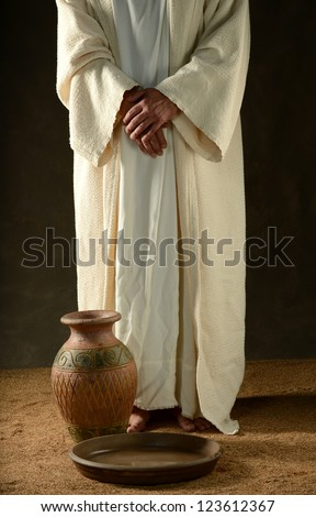 Jesus standing with his hands crossed and with a jar and bowl - stock photo