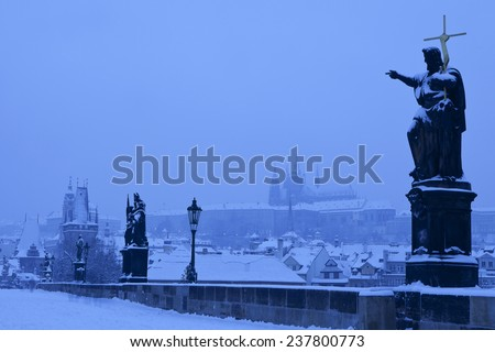 Jesus with golden cross on Charles Bridge, Pague in winter morning during snawfall - stock photo