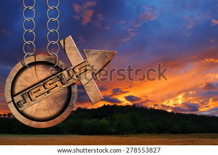 Jesus Wooden Symbol with Cross at the Sunset. Wooden symbol with cross and arrow upward and text Jesus. Hanging from a chain at a beautiful sunset over the hills with clouds - stock photo