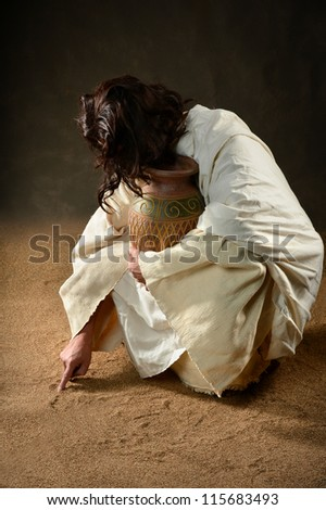 Jesus writing with finger in the sand - stock photo