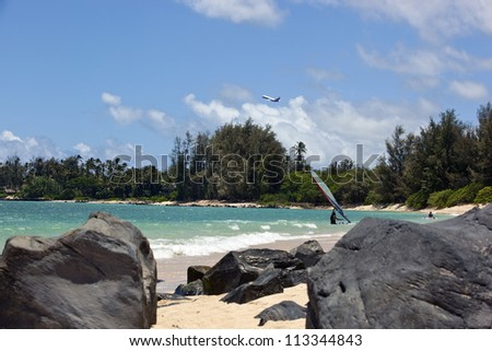 Jet Airliner taking off over wind surfers in Hawaii - stock photo