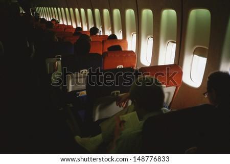 JET AIRPLANE - CIRCA 1990's: Passengers in seats on airplane - stock photo