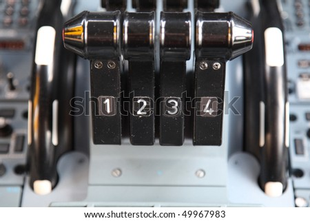 jet airplane four thrust levers in the cockpit - stock photo