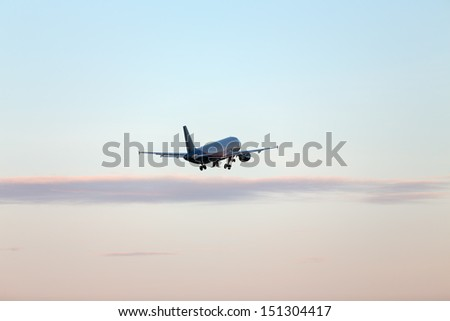 jet airplane in silhouette taking off at sunset - stock photo