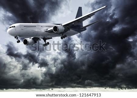 Jet in a dark stormy sky - stock photo