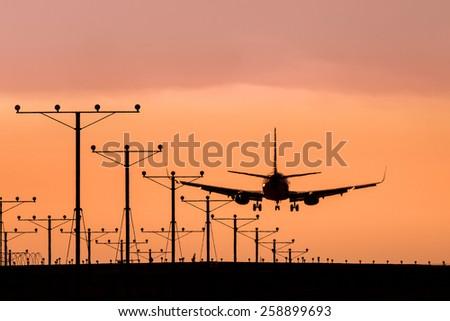 Jet Landing at Sunset - stock photo