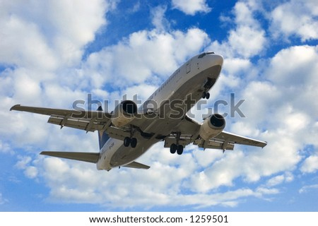 Jet landing (Boeing 737) over a cloudy sky background - stock photo