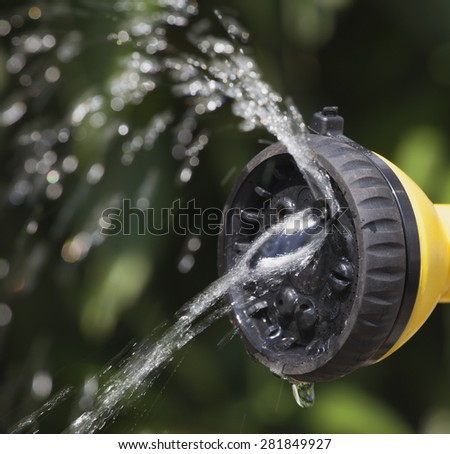 Jet of water rises from the tip of device of irrigation of garden at the sunshine on background of green plants. Rainbow in drops. - stock photo