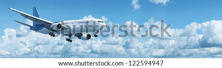Jet plane in a blue cloudy sky. Panoramic shot. - stock photo