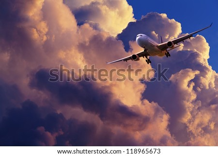 Jet plane is maneuvering for landing in a spectacular sunset sky - stock photo