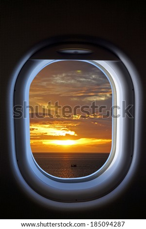 Jet plane window with sunset sky view - stock photo