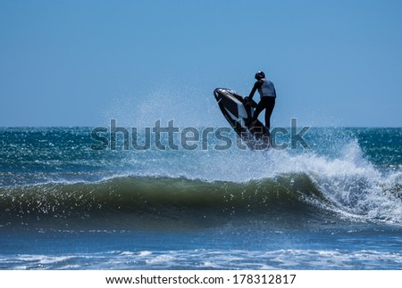 Jet ski flying over a ocean wave on a clear blue sea. - stock photo