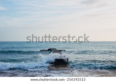 Jetty into the sea. splashing waves - stock photo