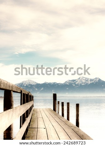 jetty on lake chiemsee with alps in background - stock photo